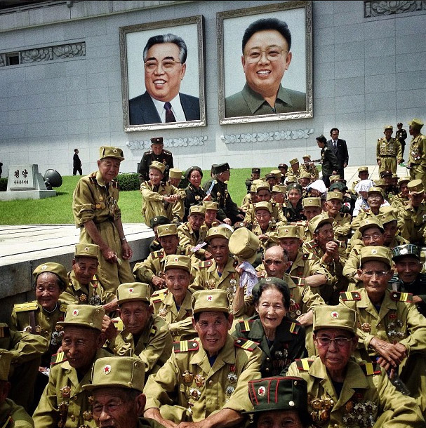 North Korean veterans of the Korean War sitting under the two Kim's portraits. Photo credits: David Guttenfelder
