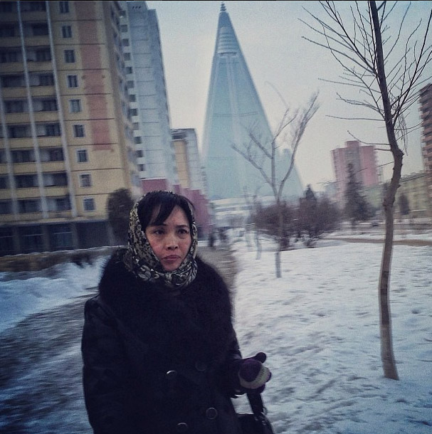 North Korean lady and yet to be completed 105-story Ryugyong Hotel in Pyongyang. Photo credits: David Guttenfelder